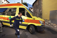 Switzerland. Canton Ticino. Dino. Day scene for a medical emergency intervention. A senior woman suffering from a broken ankle has to be brought to hospital by ambulance. A paramedic helps the ambulance's driver to get through the narrow streets. A sticker with the emergency phone number (144) to reach Ticino Soccorso. The man wears a blue uniforms and medical gloves. He works for the Croce Verde Lugano and is a volunteer specifically trained in emergency rescue. The Croce Verde Lugano is a private organization which ensure health safety by addressing different emergencies services and rescue services. Volunteering is generally considered an altruistic activity where an individual provides services for no financial or social gain to benefit another person, group or organization. Volunteering is also renowned for skill development and is often intended to promote goodness or to improve human quality of life. Medical gloves are made of different polymers including latex, nitrile rubber, polyvinyl chloride and neoprene. 28.01.2018 © 2018 Didier Ruef