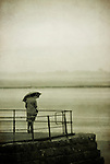 A lonely woman standing on a jetty holding an umbrella