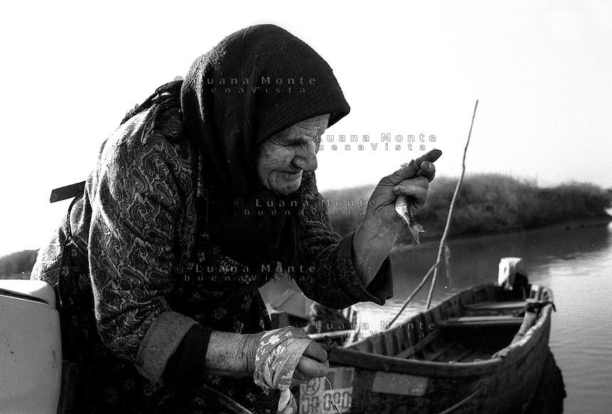 - Delta del Danubio, Jurilovca. Una donna di settantacinque anni vive sola perchè i suoi parenti sono emigrati a Milano in cerca di lavoro. Ogni mattina si reca a pescare nel piccolo porto del villaggio..- Danube Delta Area, Jurilovca. Catarina, seventy-five years old, lives alone in Jurilovca. Every morning, she moves towards the small port of the village with her fishing rod. Her son, with his family, went to Italy looking for a job and now lives in Milan.
