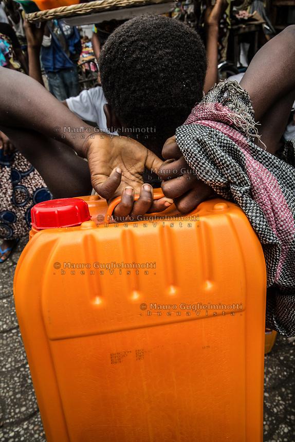 Mercato di Cotonou, un bambino trasporta una tanica di olio