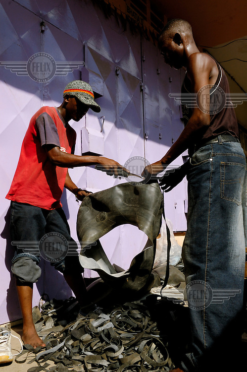 Recycling - cutting up the old rubber inner tube of a tyre into strips in a busy lane close to Kariakoo market.