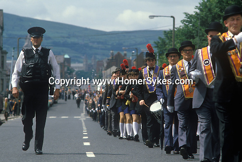Belfast The Troubles. 1980s.Orange Day Parade through outskirts of Belfast RUC  police officers give some protection.