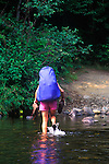 Woman on Appalachian trail, Piscataguis County, Maine carring boots across stream.
