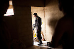 A special forces police officer, from Batalhão de Operações Policiais Especiai, or BOPE, inspects a resident's home for weapons and drugs in the Parque Alegria favela during a joint public security operation to install a Pacifying Police Unit (UPP) at the Caju favela complex in Rio de Janeiro, Brazil, Sunday, March 3, 2013. The elite police units backed by armored military vehicles and helicopters invaded the neighborhood of 13 communities in Caju favela complex early Sunday in an on-going policing program aimed to drive violent and heavily armed drug gangs out of Rio's poor communities, where the traffickers have ruled for decades.