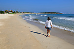 Ocean and woman walking on sandy tropical beach at Pasikudah Bay, Eastern Province, Sri Lanka, Asia