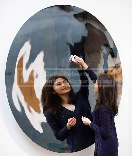 01/02/2012. LONDON, UK. A member of Sotherby's staff cleans Anish Kapoor's untitled artwork at an auction of Impressionist and Modern Art held on the 15th of February 2012. The piece is estimated to raise £700,000. Photo credit: Matt Cetti-Roberts