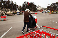 "Ventura, California, July 23, 2010 - Billy Joe McCall, a homeless veteran who was in the 82nd Airborne for two tours during the Vietnam War, pushes his Target cart past a dozens of other carts in the Target parking lot where he solicits money. Mr. McCall says that no one has ever bothered him about using the stolen cart. ""I'll just return it when I am done,"" he added.  Mr. McCall's life began to fall apart after his wife and child were killed by a drunk driver who was also high on PCP (phencyclidine piperidine). After learning the driver would only be charged with involuntary manslaughter, Mr. McCall says he paid for the man's bail and then shot him. ""I went into the bar where he hung out, laid down a .357 on the table and said go for it. He looked at me like I was crazy. But I had a .38 on my hip. He went for it and I shot him dead. I got almost three years for it."" After being released from prison, Mr. McCall's life began to unravel. He lost his painting business and says he worked for a stint with the mob in Florida. With a felony charge and a severe limp from a wound he received in Vietnam, jobs grew scarcer. He returned Texas for a period before coming to California to help take care of his ailing mother. Her medical bills and his lack of work left him with no other opportunities, but a life of the street. He says his VA pension will begin in September. ""That is going to get me off the streets once and for all."" ......"