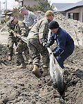 Service members from the Air Force, Navy, and Marine Corps work together April 1, 2011, to free a plastic sheet from mud and sand at a strawberry farm in Hachinohe, Japan. (Photo by USAF/AFLO) [0006]