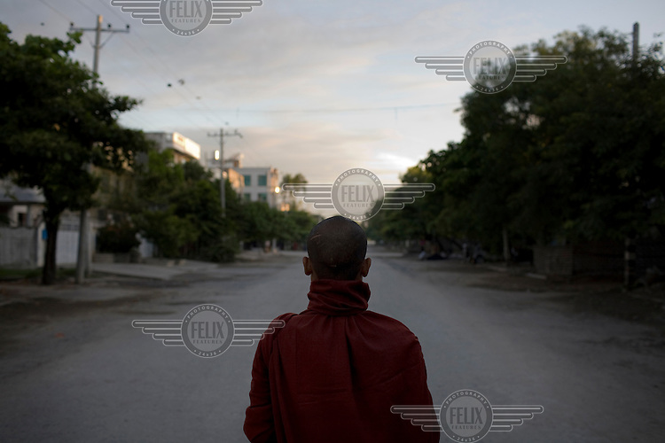 A monk on his morning alms round in a suburb of Mandalay.