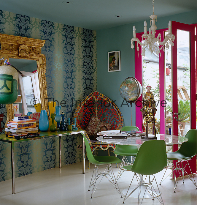 Shocking-pink doors electrify the dining room's mix of modern furniture and baroque wallpaper