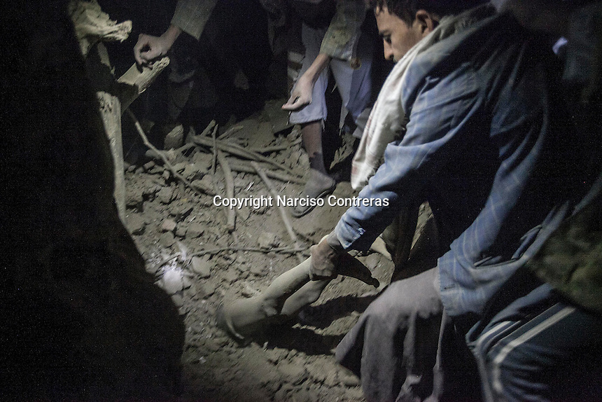 July 15, 2015 - Sa'dah, Yemen: The younger brother of Bashar Al Asadi, 14 years-old (not pictured), is seen under the rubble of a house building after it was hit by a fighter jet from the Saudi-led coalition in the northern city of Sa'dah, the stronghold of the Houthi movement in Yemen. The family of Bashar was buried under the rubble during the attack. Two members of his family, the mother (not pictured) and his brother died from their injuries, while his sister (not pictured) survived. (Photo/Narciso Contreras)