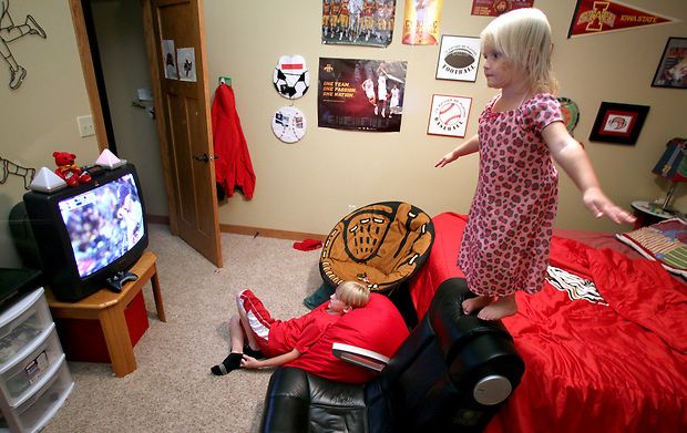 Ella Jacobs, 3, balances atop a chair while her brother Justin, 9, watches baseball in his bedroom.  Their mother, Heather Jacobs, lost her husband, Eric, in a plane crash in 2006 when she was eight months pregnant with their youngest, Ella, and has since been raising her five young children on her own.