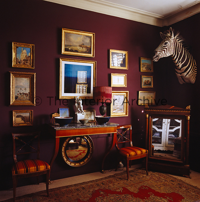 The walls of the bedroom have been painted a dramatic deep aubergine, the perfect backdrop for a collection of gilt-framed paintings and prints and the head of a zebra