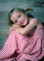Smiling young girl in red checked gingham dress. Leoni. Germany.