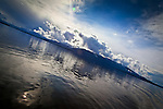 Inside Passage in early morning.  Sun peaks through a dramatic clouds over an island. SE Alaska.