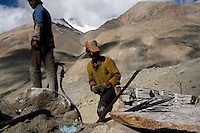 "Workers break rocks to build the road to Everest Base Camp.China started building a controversial 67-mile ""paved highway fenced with undulating guardrails"" to Mount Qomolangma, known in the west as Mount Everest, to help facilitate next year's Olympic Games torch relay."