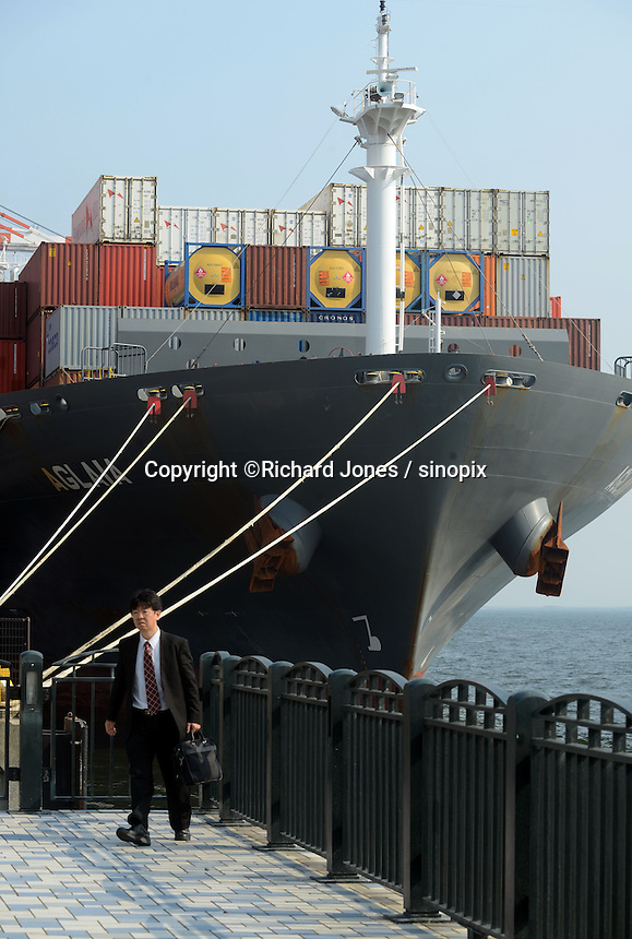A businessman is walking by the big ship at the port, Tokyo Bay, Japan
