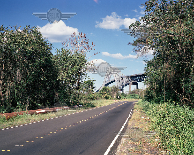 A road near Venado Beach in the Panama Canal Zone with, in the background, the Bridge of the Americas. Originally known as the Thatcher Ferry Bridge, it is a road bridge that spans the Pacific entrance to the Panama Canal. Completed in 1962, it connects the North and South American landmasses. <br /> <br /> The Panama Canal Zone is an area extending 8kms out, in each direction, from the waterway's central line, was a territory controlled by the United States between 1903 and 1979. After a 20 year period of joint administration, the Canal came under the full control of Panama in 1999. The Canal opened to shipping in 1914 and during its tenure was of great strategic importance to the US, enabling it to rapidly move its naval fleet between the Atlantic and Pacific Oceans. However, its economic value came not directly from shipping fees but from the stimulus to trade that the waterway created. One hundred years after it opened in 2014 it is due to have its locks upgraded to cater for the super sized container ships of the 21st Century.  <br /> During the era of American administration thousands of US citizens populated the Canal Zone, living and working under US law in towns built to American standards. Not all of these people returned north after the canal came under full Panamanian control many stayed on, their identities tied to the region.
