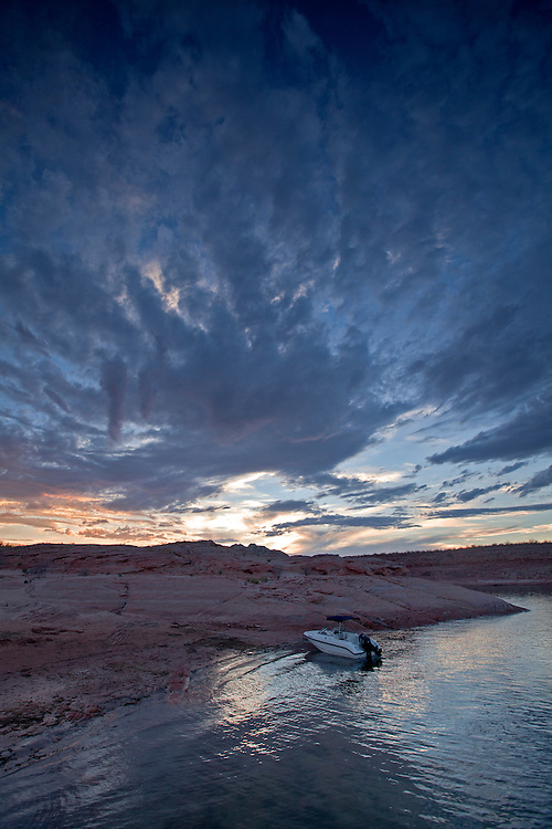 As a monsoon storm approaches, a speed boat rests along Warm Creek Bay on Lake Powell within the Glen Canyon National Recreation Area, Utah, USA