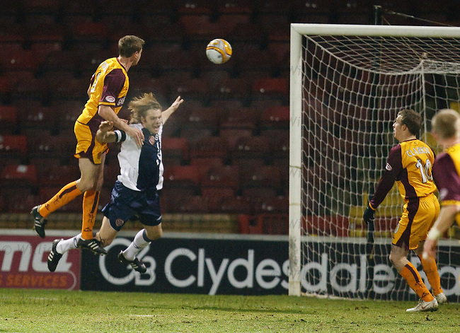 Chris Porter rises above Robbie Neilson to score for Motherwell