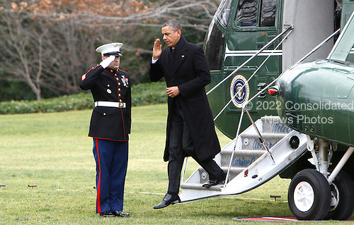 United States President Barack Obama salutes the Marine Guard as he returns to the White House from a Christmas vacation in Hawaii on December 27, 2012..Credit: Dennis Brack / Pool via CNP