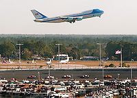 Air Force One with President George W. Bush aboard takes off from Daytona International Airport as NASCAR Nextel Cup series racers go through turn two during the Daytona 500 at Daytona International Speedway in Daytona Beach, Fl.
