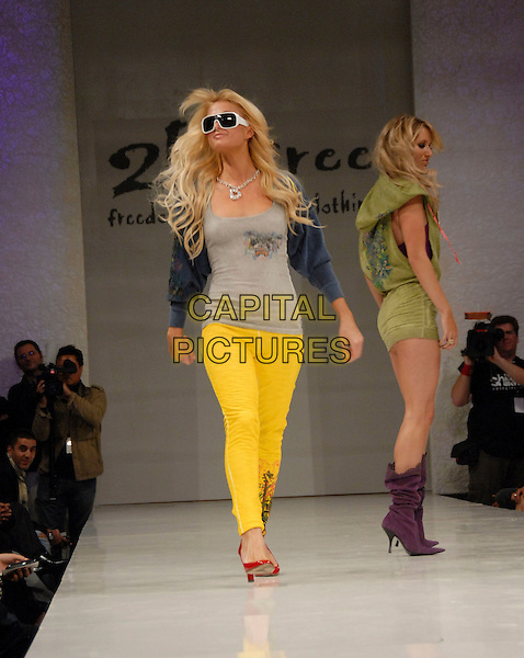 PARIS HILTON.attends The 2 B Free Fashion Show held at Boulevard3  in Hollywood, LA, California, USA, March 19 2007..full length catwalk runway modelling yellow leggings suglasses grey top red shoes.CAP/DVS.©Debbie VanStory/Capital Pictures