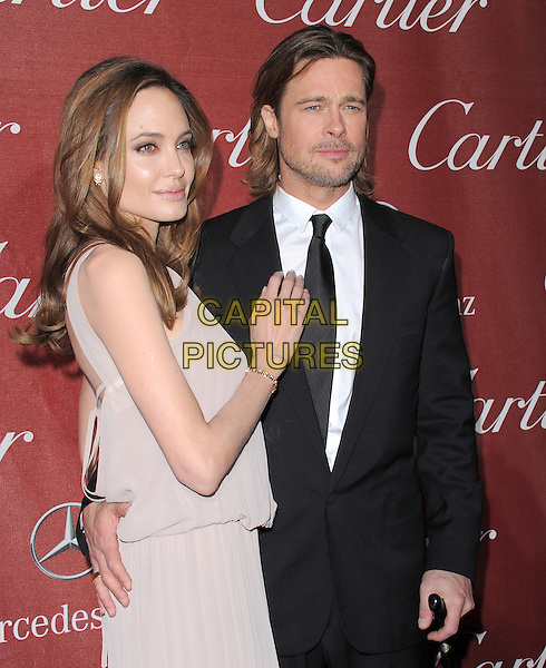Angelina Jolie & Brad Pitt .attending the 2012 Palm Springs International Film Festival Awards Gala held at The Palm Springs Convention Center in Palm Springs, California, USA, January 7th 2012. .arrivals half length beige greige dress  halterneck crutch walking stick cane  black suit tie couple brangelina angie  side gold bracelet arm around grey gray .CAP/RKE/DVS.©DVS/RockinExposures/Capital Pictures.