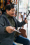 Music instrument store owne plays Erhu Chinese fiddler in Shanghai, China