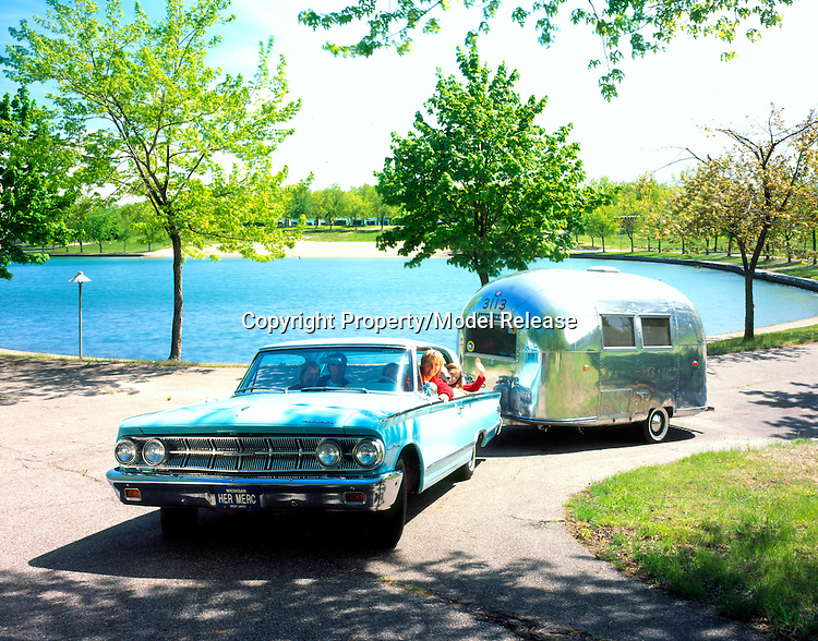 1963 Mercury pulling a 1963 Airstream Bambi travel trailer while the passengers of the Mercury are smiling and waiving.