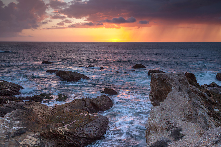 A curtain of rainwater from the dark clouds enhances the drama of the golden sunset offshore at Montana de Oro state park on California's central coast.