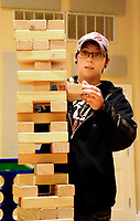 Janelle Jessen/Herald-Leader<br /> Bri Gibbens skillfully took a block out of a giant game of Jenga during Family Game Night on Friday.