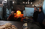 A Palestinian baker makes bread using a wood-fired oven at his traditional bakery in Rafah in the southern Gaza strip, on January 14, 2017. Power shortages in the Palestinian enclave have occurred repeatedly in recent weeks, with homes in Gaza City typically getting around four hours a day - rather than at least eight normally. Photo by Abed Rahim Khatib
