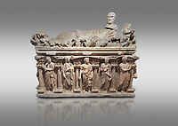 "Roman relief sculpted sarcophagus with kline couch lid with a reclining male figuer depicted, ""Columned Sarcophagi of Asia Minor"" style typical of Sidamara, 3rd Century AD, Konya Archaeological Museum, Turkey. Against a grey background"