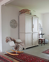 An Eames rocking chair is juxtaposed with a traditional painted cupboard in the dining room
