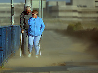 Pictured: A couple struggle to walk against the strong wind and sand blasted from the beach on Oystermouth Road from the beach in Swansea, UK. Monday 16 October 2017<br /> Re: Remnants of Hurricane Ophelia are expected to bring strong gusts of wind to Wales when it hits Britain's shores.<br /> The hurricane, making its way from the Azores in the Atlantic Ocean, will have weakened to a storm when it arrives.<br /> A Met Office amber &quot;be prepared&quot; warning has been issued in some areas bringing &quot;potential danger to life&quot;.