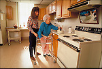 physical therapist helping elder woman in kitchen
