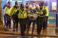 Pictured: A man is handcuffed and removed by police officers in Wind Street, Swansea, south Wales, UK. Friday 21 December 2018<br /> Re: Black Eye Friday, also known as Mad Friday or Black Friday which is the last Friday before Christmas Day.