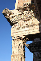Rome, Fora: A lateral view of the high part of one of the so-called Colonnacce, the ancient Roman columns that decorated the surrounding wall of the Forum of the emperor Nerva  (I century AD). It was a sunny day and in particular the bas-relief that lies on the column top is enlightened. Digitally Improved Photo.