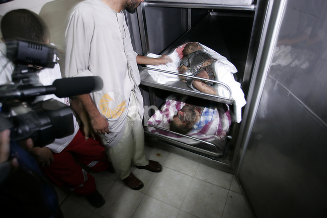 Palestinians look at the body of militant Kamal al-Nayrab, secretary-general of the Gaza-based group the Popular Resistance Committees (PRC), at the morgue in the al-Najar Hospital in the southern Gaza Strip town of Rafah, on August 18, 2011, following an Israeli airstrike that killed six Palestinians medics said. The strike came as Israeli military forces fought to regain control in southern Israel after at least three attacks that killed seven people. Photo by Abed Rahim Khatib