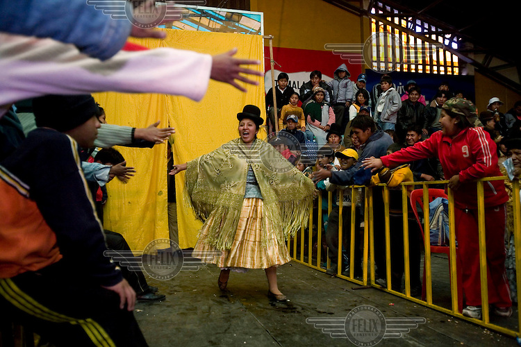 26 year old wrestler Juanita la Carinosa (fighting name), Mery Llanos Saenz (real name) encourages the crowd as she enters the fighting area at the Multifuncional building in El Alto. Mery is a Cholita, a wrestler of native Aymara descent. When Cholitas fight they wear traditional costume - a colourful dress and a dark bowler hat.