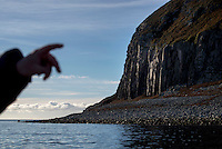 A fisherman points to the granite rock formations on the south-west side of Ailsa Craig, an unihabited volcanic island that is the source of the granite used to make most of the world's curling stones, including those used every four years in the Winter Olympics.