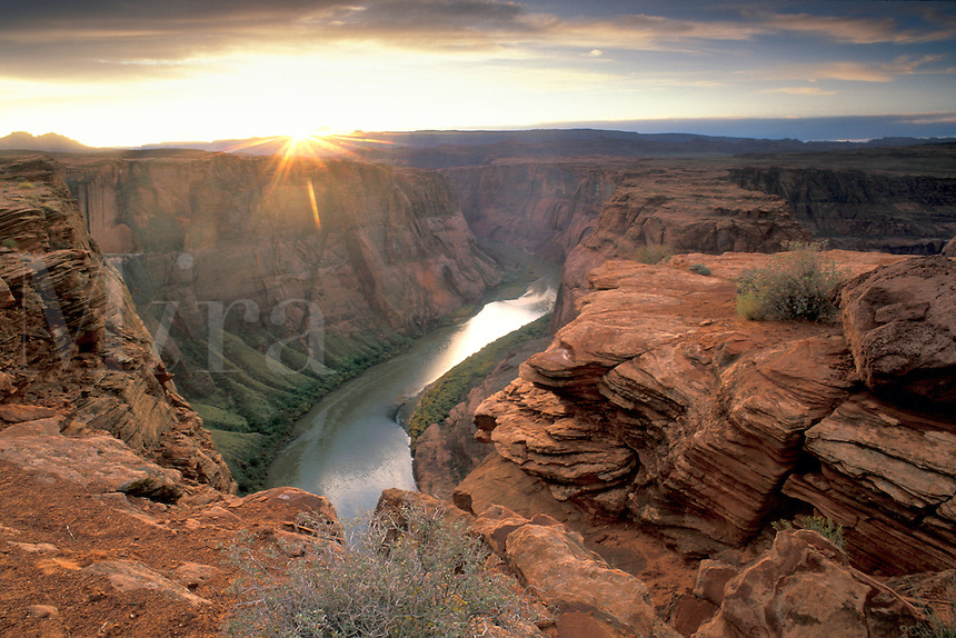 Sunset and clouds over steep red sandstone rock cliffs along a bend in the Colorado River canyon, near Page, Arizona.