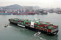 A container ship arrives at the port of Hong Kong, China. Asian shipping shares slumped Tuesday, reflecting a decrease in global demand for commodities and an industry suffering from excess capacity due to the global downturn in trade..