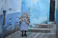 Elderly woman with a walking stick in a narrow street in the medina or old town of Chefchaouen in the Rif mountains of North West Morocco. Chefchaouen was founded in 1471 by Moulay Ali Ben Moussa Ben Rashid El Alami to house the muslims expelled from Andalusia. It is famous for its blue painted houses, originated by the Jewish community, and is listed by UNESCO under the Intangible Cultural Heritage of Humanity. Picture by Manuel Cohen