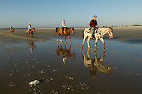 A group of people ride horses along the beach at sunise in Amelia Island, FL