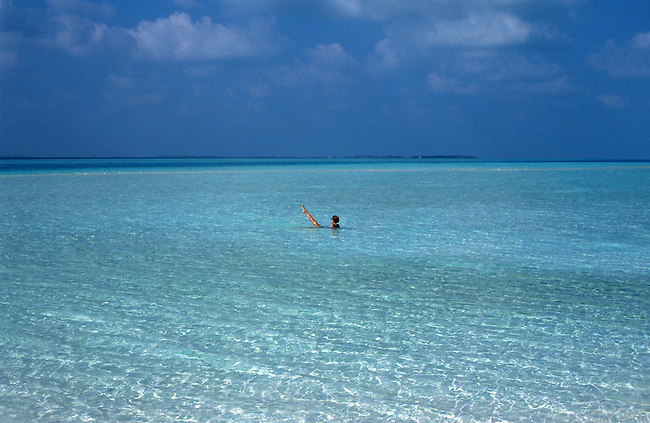 Rihiveli (atoll sud Male), une femme dans l'eau. *** Rihiveli (south male atoll), woman in sea.