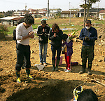 "Ms. Mayumi Miura, 56, center, and her friends and relatives pray before pull out her father's body from a temporary grave yard in Ishinomaki, Miyagi. One month after the earthquake, they finally managed to arrange a family funeral. ""We are so relieved that we are finally able to put him into his grave,"" Ms. Mimura said. His father was washed away by tsunami in front of his wife, Mrs. Katsumi Saito, 69. <br />