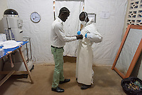 "Hygienist Eddie Johnson helps hygienist Augustine T.J. Bindi don his PPE with his portrait on the front before he enters the ""red zone"" in which suspected and confirmed patients with Ebola are cared for at the ELWA II ETU (Ebola treatment unit) in Monrovia, Liberia on Tuesday, March 3, 2015. Occidental College professor Mary Beth Heffernan's PPE Portrait Project involves creating wearable portraits of health care workers who must wear PPE. <br /> (Photo by Marc Campos, Occidental College Photographer) Mary Beth Heffernan, professor of art and art history at Occidental College, works in Monrovia the capital of Liberia, Africa in 2015. Professor Heffernan was there to work on her PPE (personal protective equipment) Portrait Project, which helps health care workers and patients fighting the Ebola virus disease in West Africa.<br />