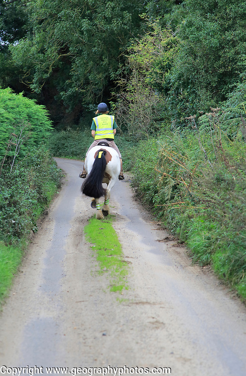 Woman riding a horse down quiet country lane, Eyke, Suffolk, England, UK